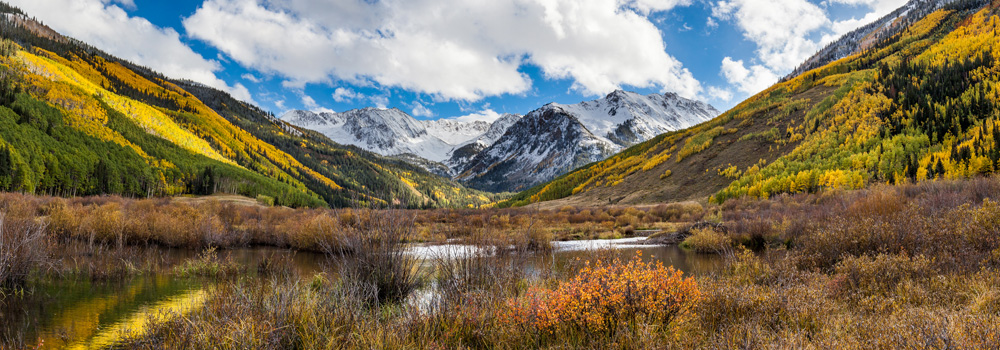 Colorado mountains with autumn colored leaves and snow on the peaks