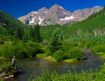A fly fisherman with the Maroon Bells in the background