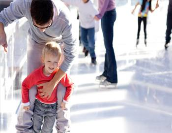 Man holding onto son at an ice skating rink