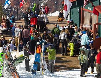 Skiers and snowboarders standing outside a lodge