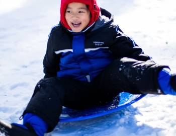 A child sledding down a snowy hill in Aspen